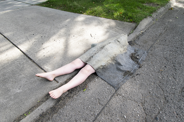 This is a picture of a pair of fake human legs as they are emerging from the sidewalk and street by Richard Haley